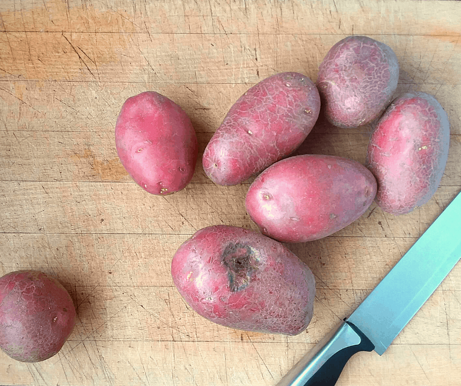 Red potatoes on a cutting board with a knife