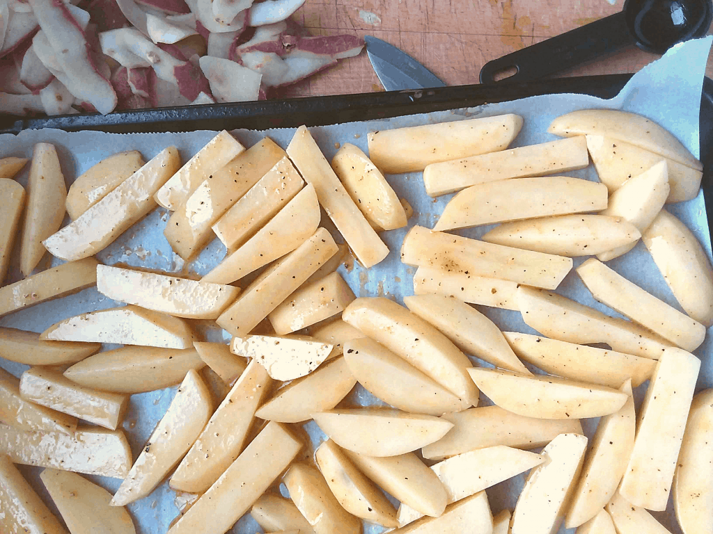 seasoned potato slices on a baking sheet