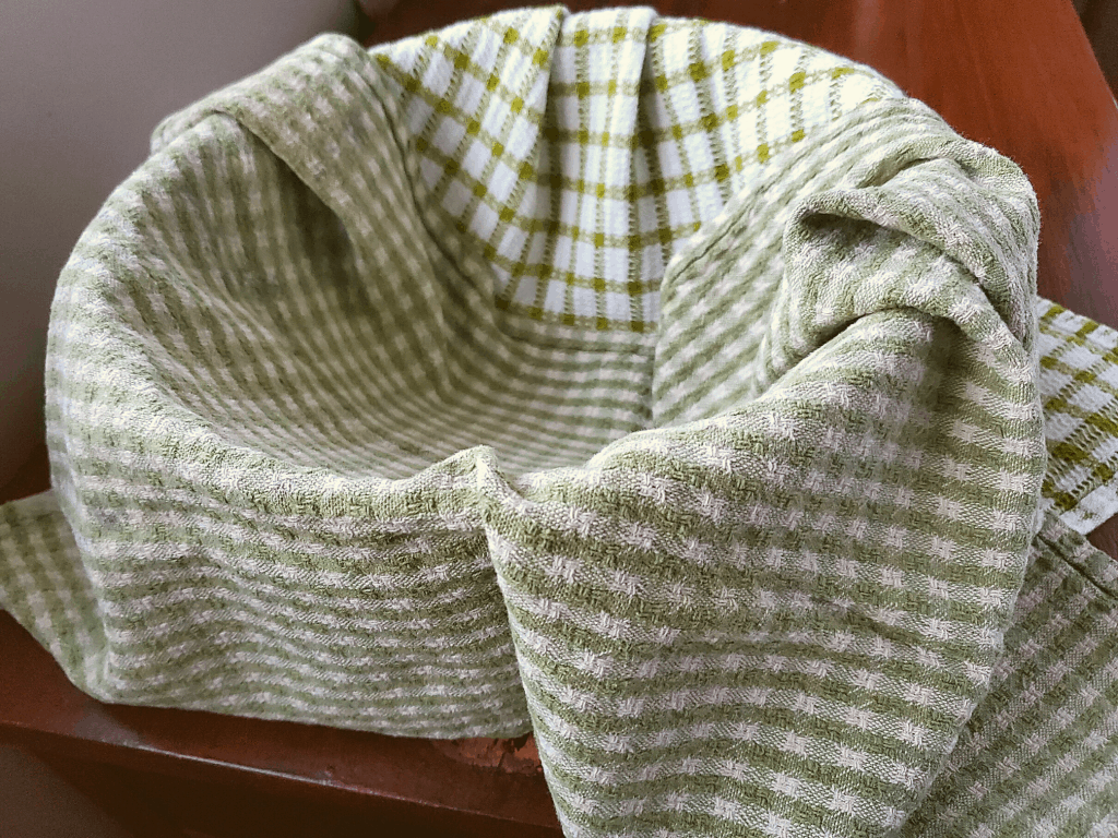 A bowl lined with 2 tea towels