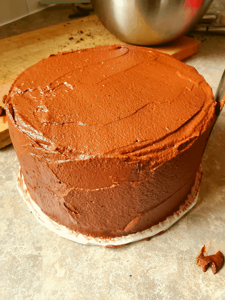 A chocolate cake being frosted