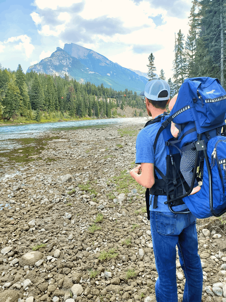 Man and child in hiking backpack looking at a mountain