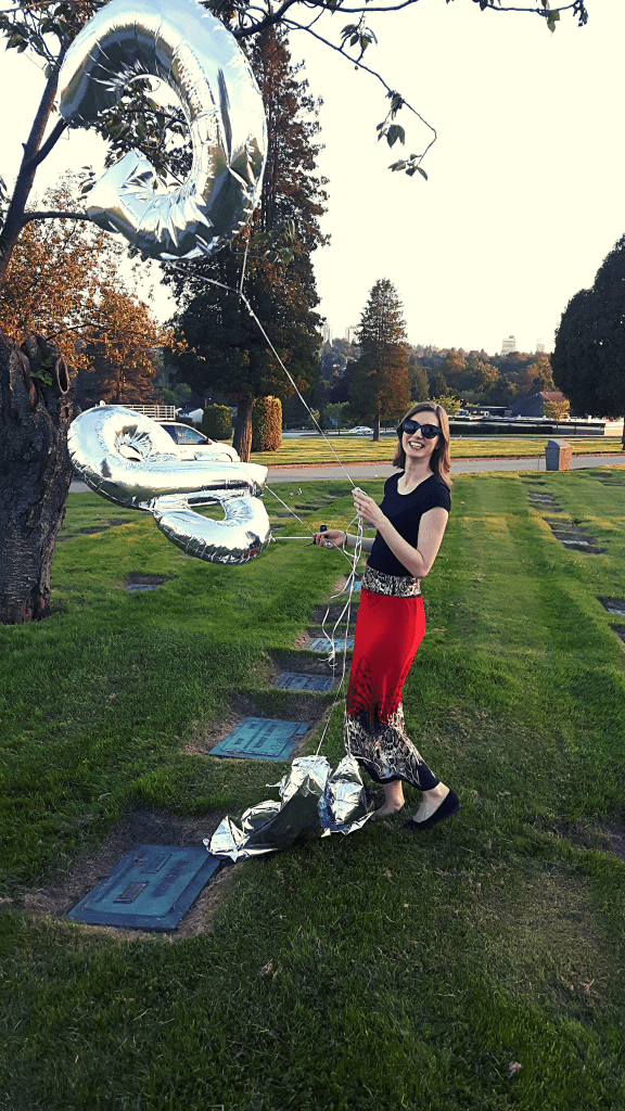 woman holding giant silver balloons in a cemetary