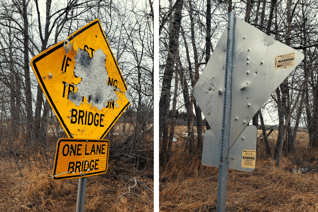 A road sign with many bullet holes