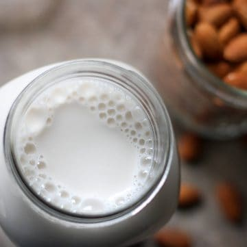 almond milk in jar with almonds in background