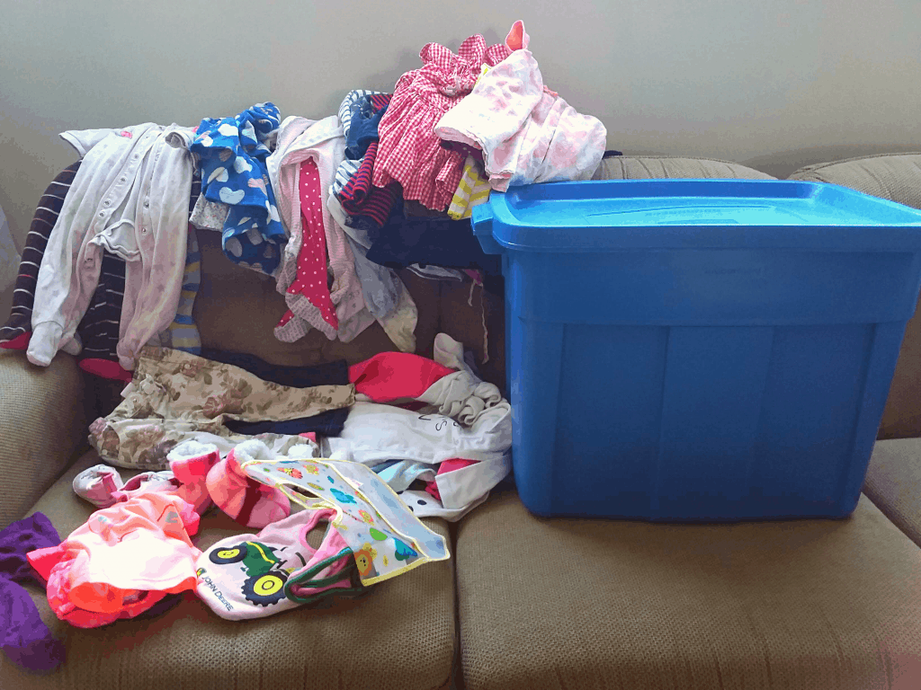 A large amount of baby clothes and rubbermaid bin on a couch, ready to sort