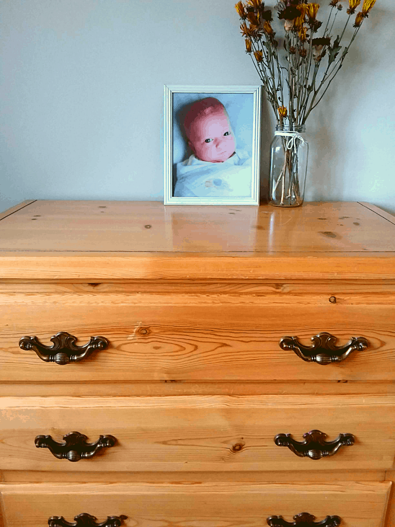 Dresser with baby photo and flowers on it