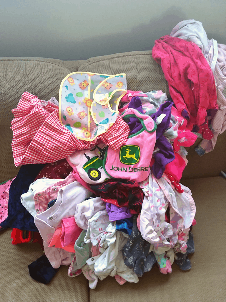 Pile of baby clothes on couch for donation