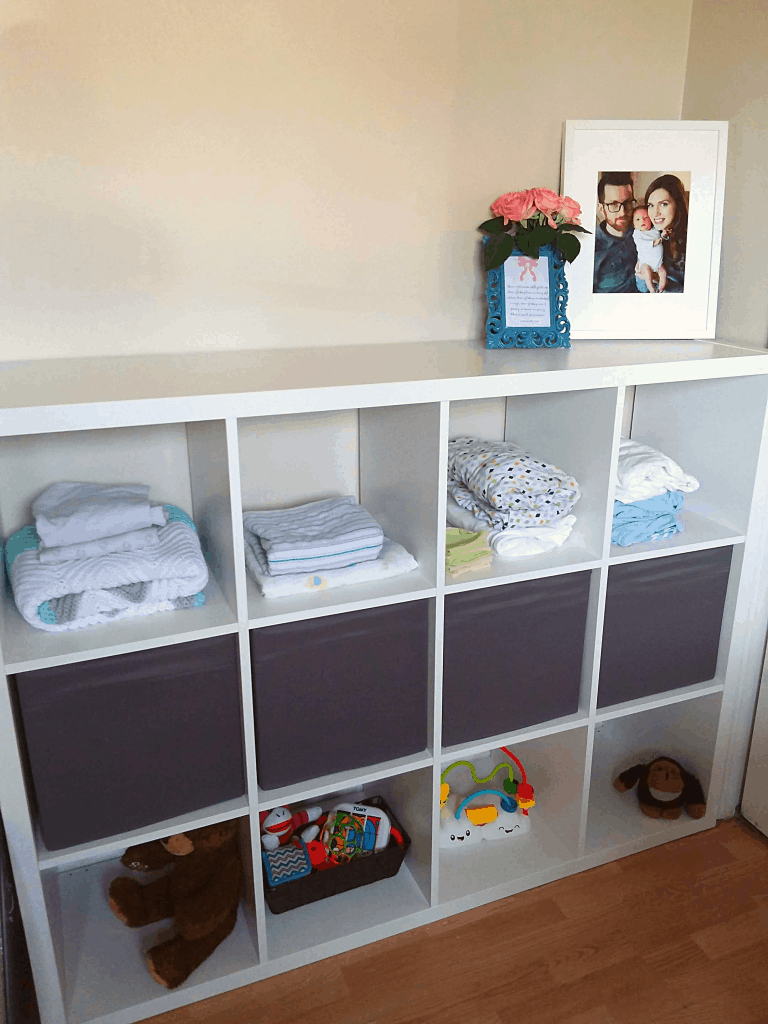 Cube shelf unit filled with organized baby items
