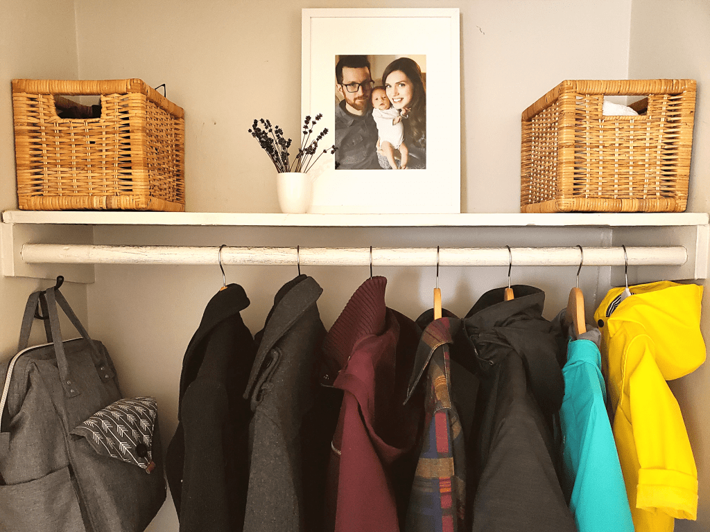 Entryway closet organization with baskets, hooks, hangers and some decor