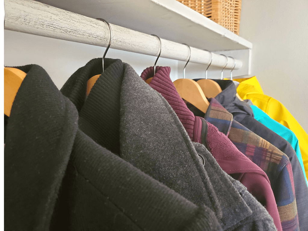 close up of coats on hangers in entryway closet