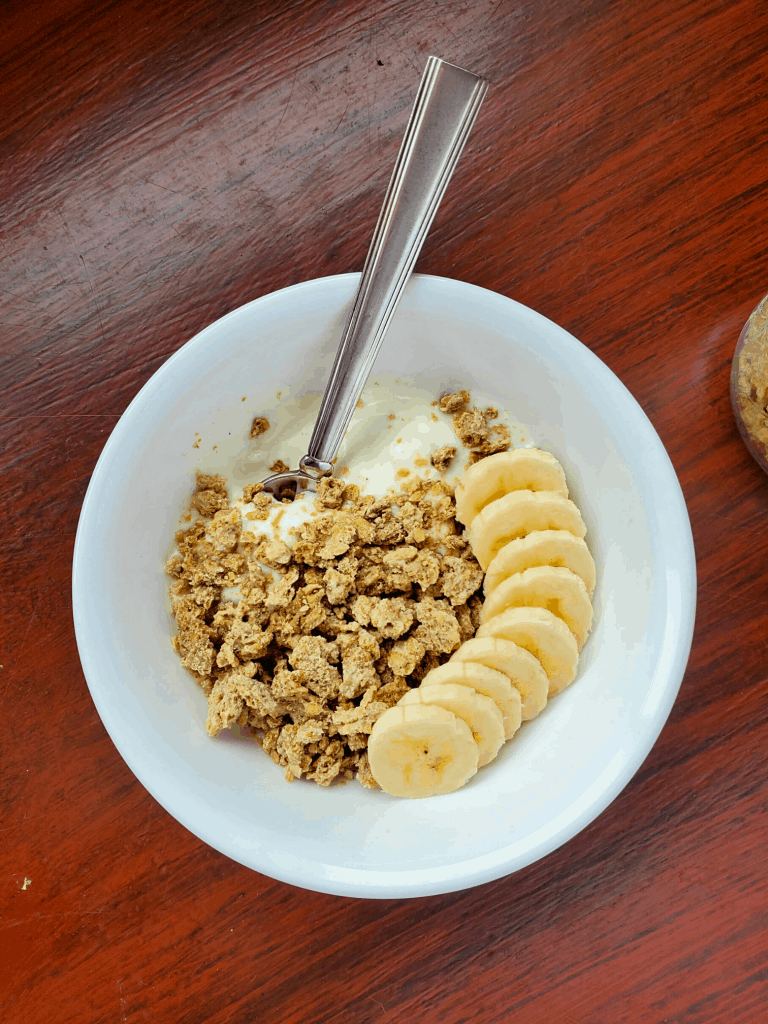 Granola in a bowl with yogurt and bananas and a spoon