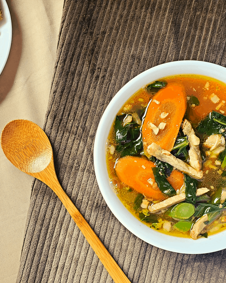 chinese vegetable soup in a bowl with spoon and crackers
