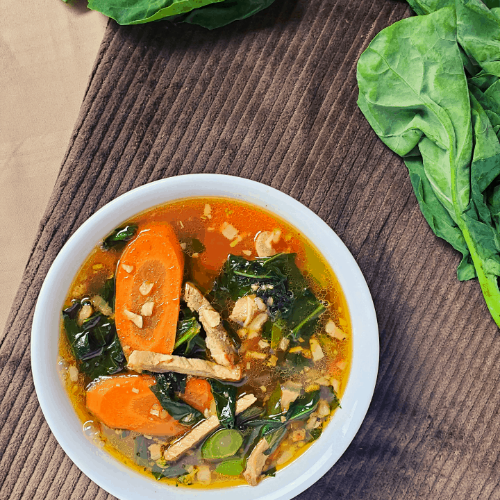 chinese vegetable soup in a bowl with chinese broccoli on the side