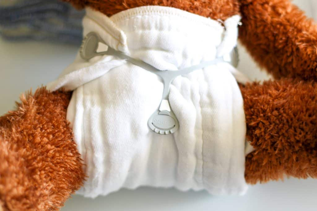 a teddy bear wearing a cloth diaper prefold and snappi
