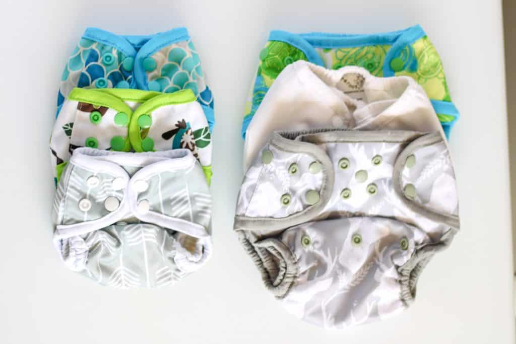 stack of newborn diapers beside stack of one-size diapers