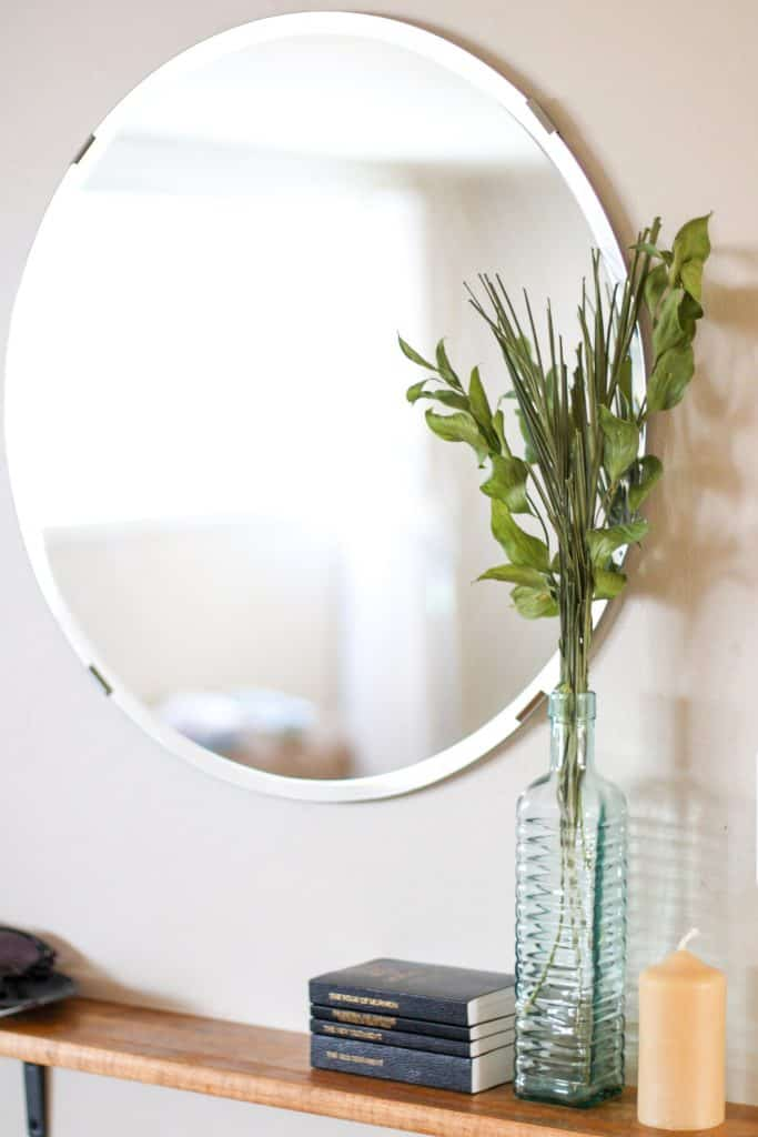 Dried greenery in a vase on a shelf by a mirror, books and candles