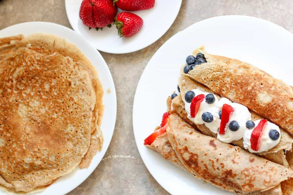crepes on a plate with fruit, a stack of crepes on a plate and a plate of strawberries