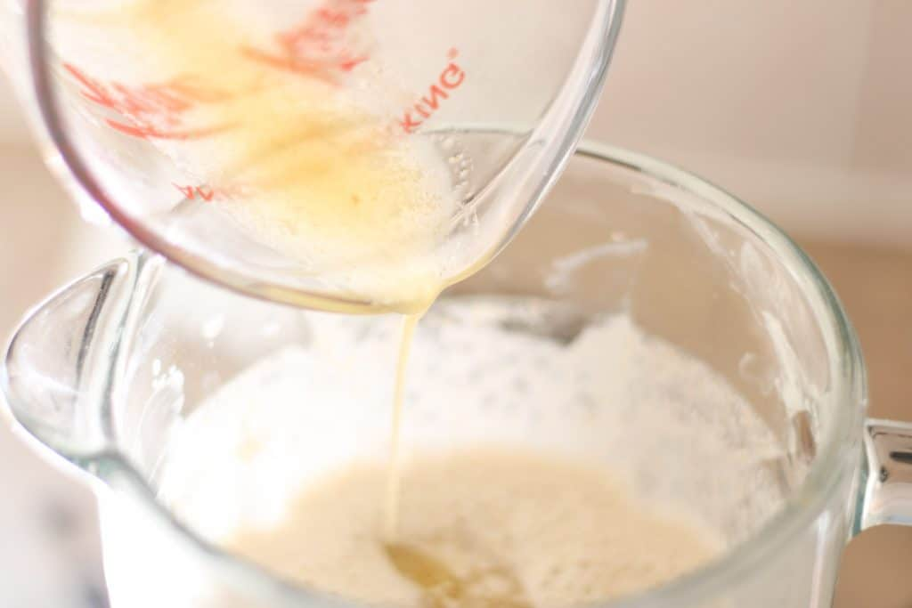 pouring butter into crepe batter