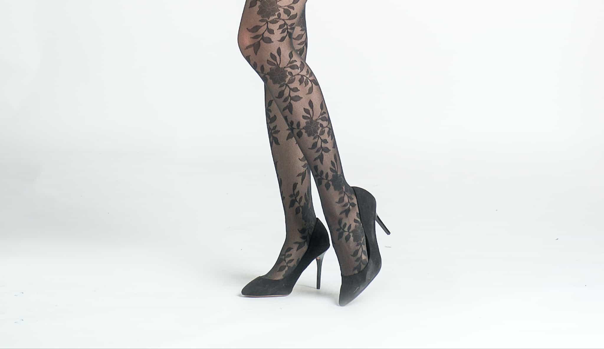 woman's legs wearing black flowery tights with black high heels
