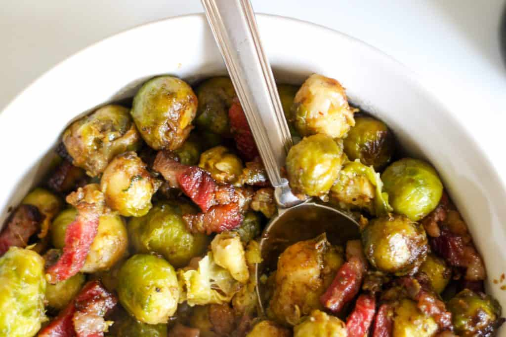 roasted brussels sprouts with bacon in a serving dish with spoon