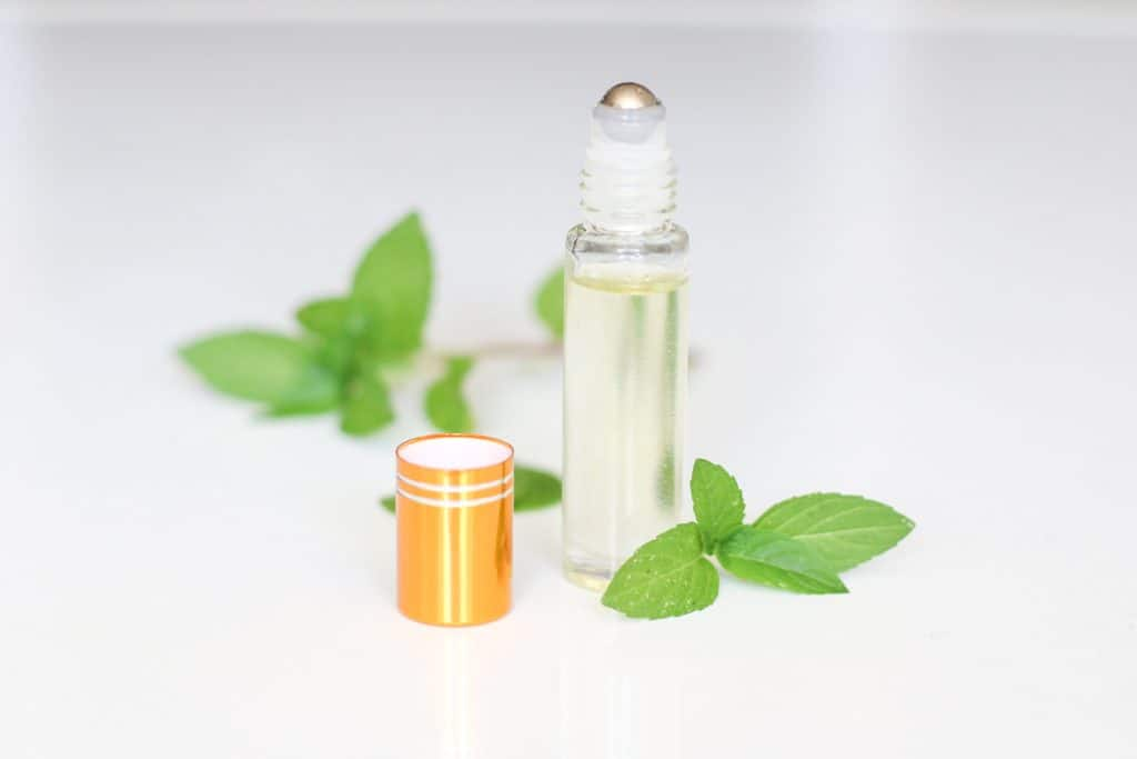 diy lip oil in roller bottle with mint leaves around