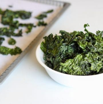 bowl of kale chips with dehydrator tray in the back