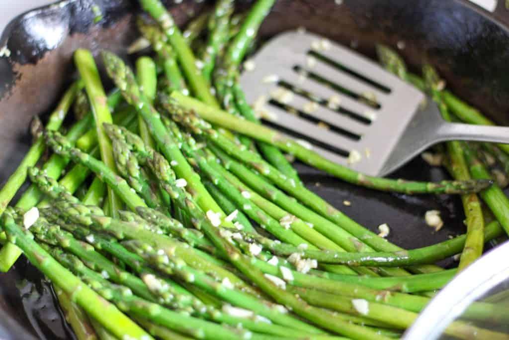 Stirring garlic into asparagus