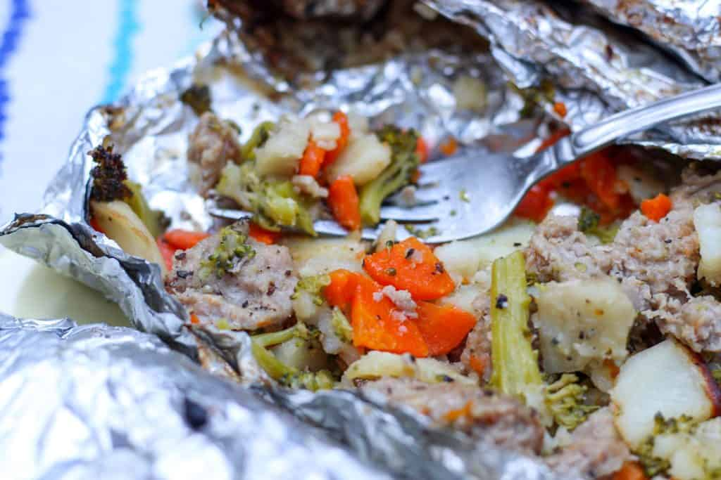 close up of veggies and sausage cooked in foil packet