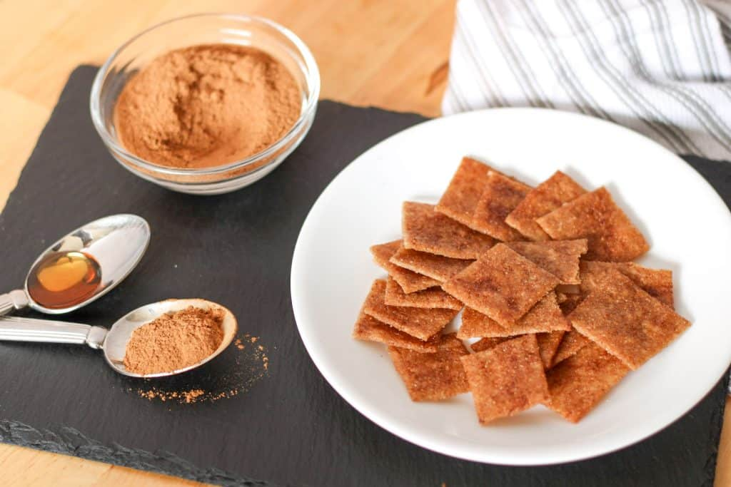 maple cinnamon crackers on plate, spoon of cinnamon and maple syrup