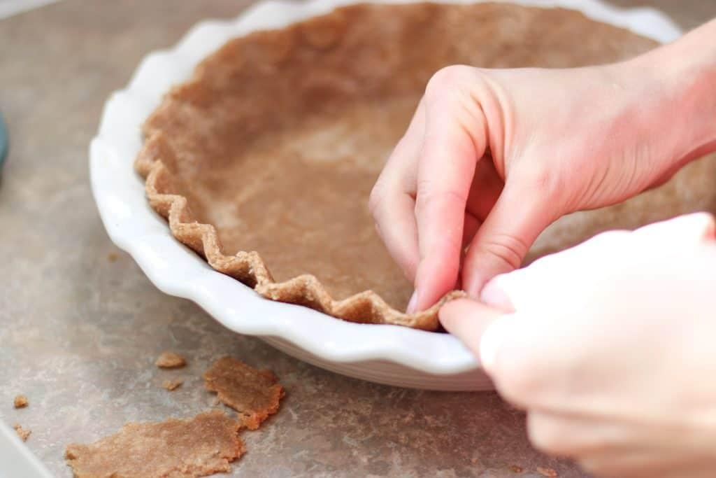 fluting edge of pie crust with fingers