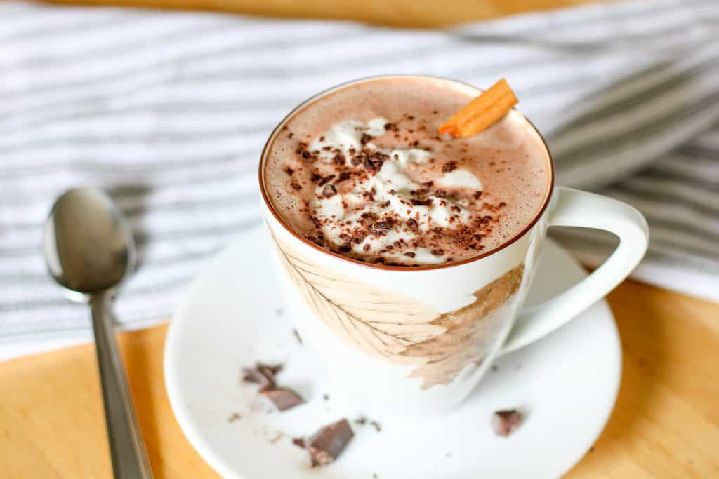 hot chocolate with whipped cream and cinnamon stick