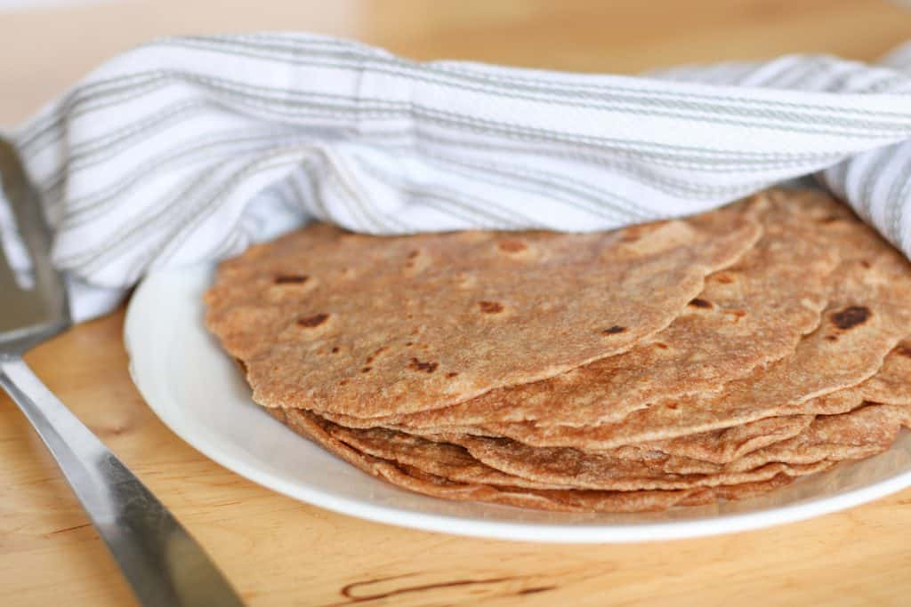 sprouted wheat tortillas on plate under tea towel