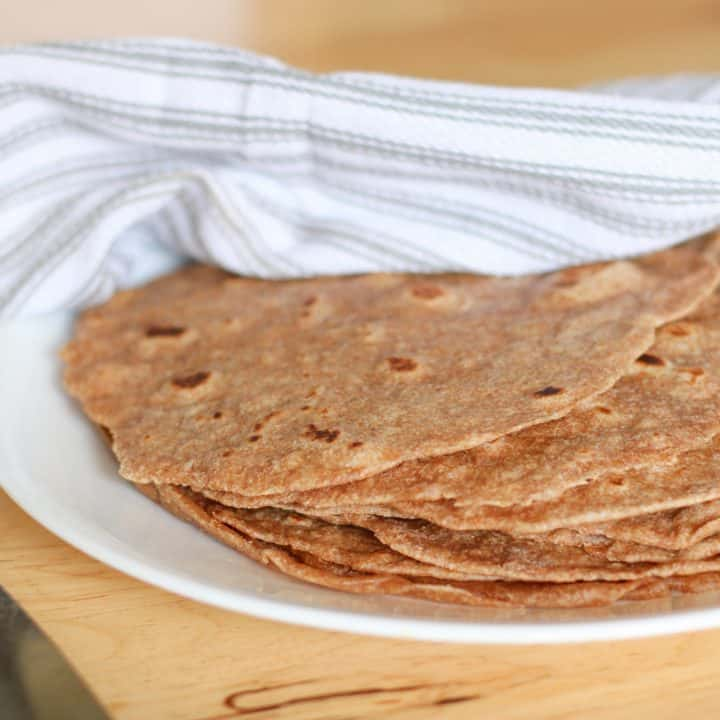tortillas on plate covered with tea towel