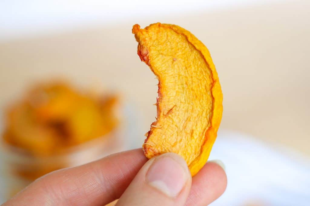 holding a slice of dried peach